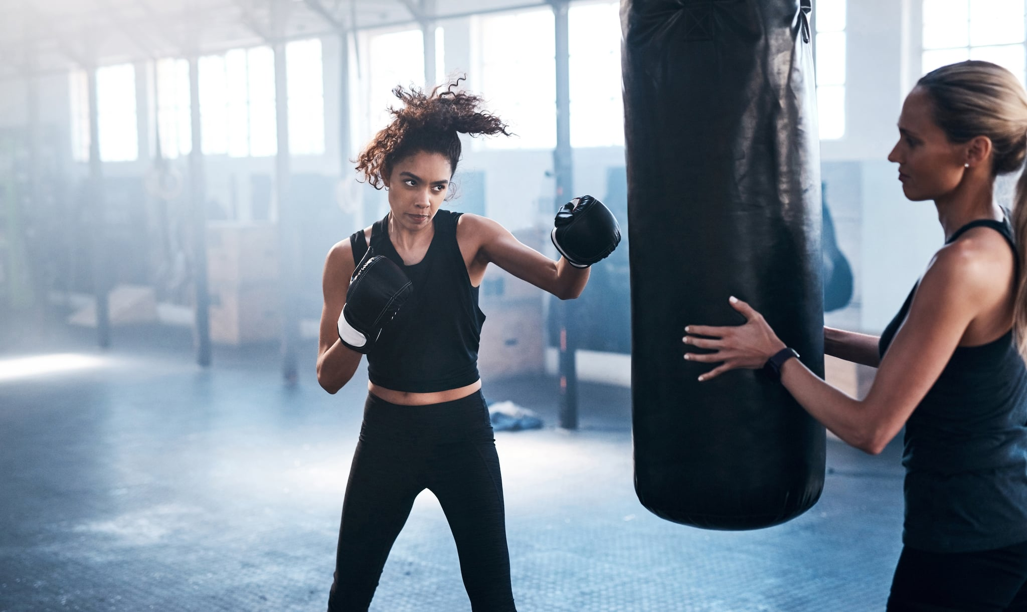 Cropped shot of an attractive and athletic young female boxer working out with her trainer in the gym