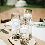 For a pretty table centerpiece, place pebbles in a glass, fill with water, and add in floating candles.