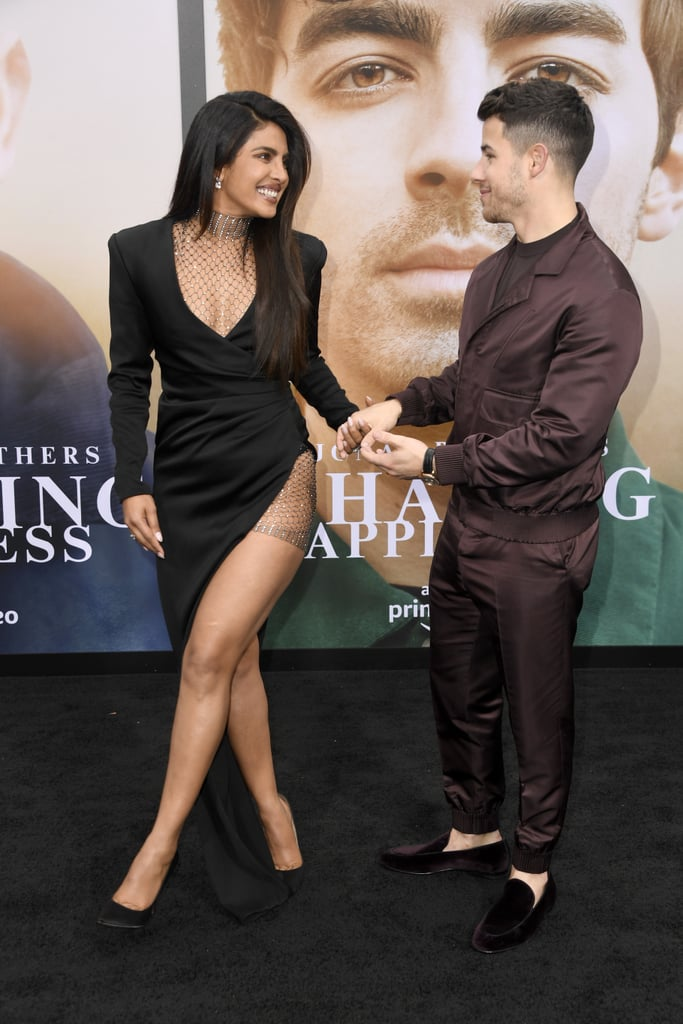 Priyanka Chopra certainly knows how to make an entrance. The 36-year-old actress recently supported her husband, Nick Jonas, at the premiere of his Amazon documentary Chasing Happiness, along with her sisters-in-law Sophie Turner and Danielle Jonas. Each woman let their individual sense of style shine on the red carpet, and Priyanka's black Galia Lahav dress was far from ordinary.  Priyanka chose a sultry high-low dress for the occasion, which featured a plunging neckline and fishnet detailing. The jeweled fishnet adorned her décolletage like a turtleneck and accented the thigh-high slit on her left side. She paired the ensemble with subtle Jimmy Choo pumps and sparkling diamond Chopard jewelry, letting the dress's sexiest elements do the talking. Ahead, see Pri's look from all angles. We bet it left Nick totally speechless.  Related: Priyanka Chopra's Date-Night Outfit Is White-Hot — Did You Expect Any Less?