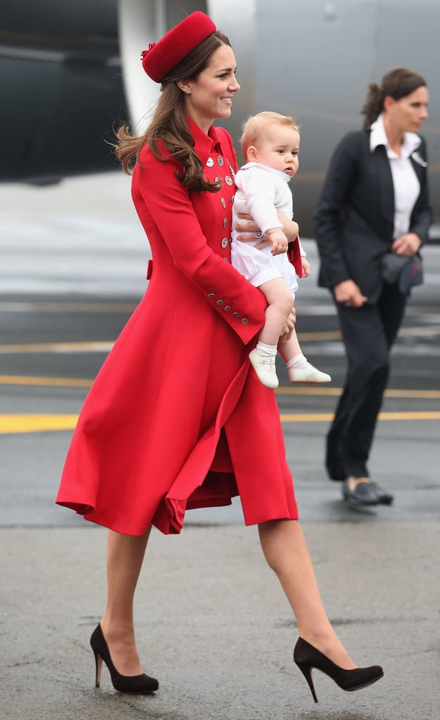 Kate Middleton made a grand entrance in New Zealand on Monday, stepping off a New Zealand Airforce Plane at the Wellington Military Terminal in a bright red Catherine Walker coat and Gina Foster hat with adorable Prince George in her arms. George wore an ivory ensemble for the big moment, which happened just hours after the family transferred aircraft during a stop in Sydney, Australia earlier this morning. During the pitstop, Prince William held their belongings — including George's cute Save the Koala bag! Covered up in a dark blue knitted sweater and pants, George matched his dad, who suited up for the big occasion. Meanwhile, Kate donned a patterned dress and beige heels. Prior to landing in Sydney, the family traveled first class on a 25-hour commercial Quantas Airways flight from London accompanied by their staff, including George's nanny.  Today marks the beginning of George's first royal tour. After their welcoming ceremony in New Zealand on Monday, the family will rest before their first outing on Wednesday. They'll return to Australia on April 16, where they will embark on the second part of their three-week tour. In total, the royals will be seen at 45 events in 13 towns and cities, providing plenty of opportunities for the public to see 8-month-old George. Just last weekend, anticipation for the trip reached a fever pitch when the royals released an official portrait of George, showing him with his parents as they sat near a windowsill in their Kensington Palace apartment. As you await more adorable moments in the coming weeks, check out the George photo ops we're hoping for, inspired by William's first royal trip Down Under as a baby, and get all the details about their packed schedule!