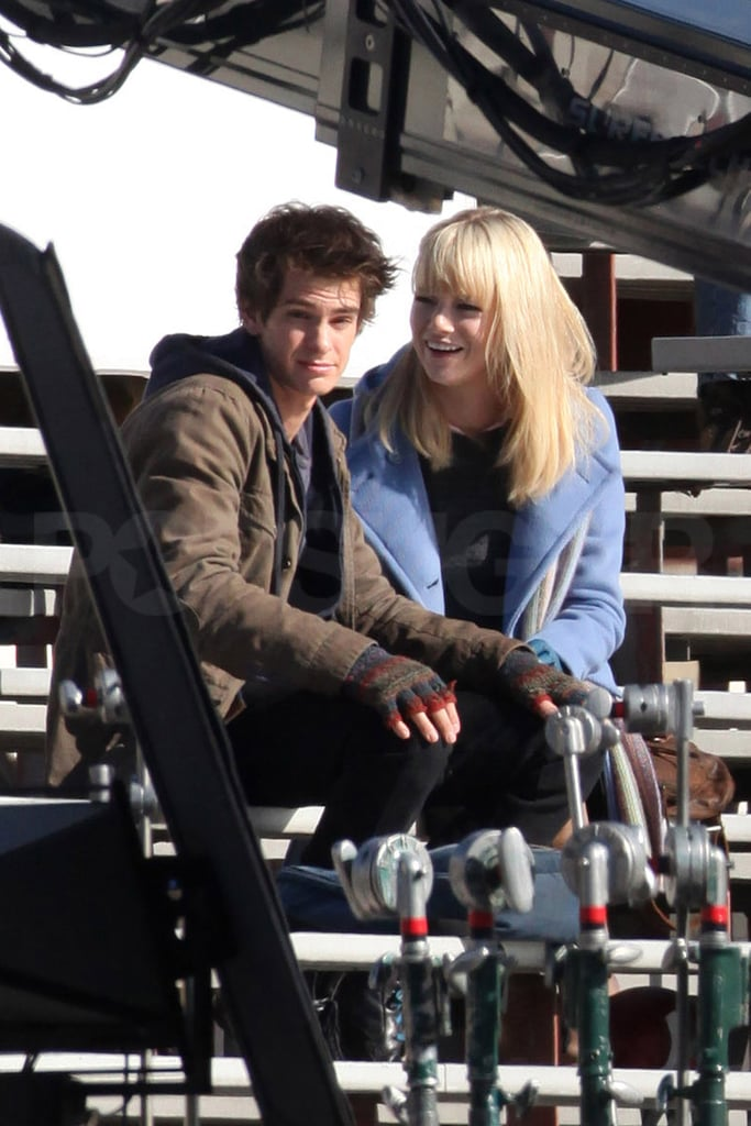Emma Stone laughed on set of the new Spider-Man reboot in LA yesterday, as she filmed a scene with Brit actor Andrew Garfield. He's your one to watch for 2011 and he certainly kept newly-blonde Emma smiling as he snuck a kiss in the scene. This is our first exciting look at Andrew as Peter Parker, though Emma was spotted filming as Gwen Stacy last month. Barcroft Media