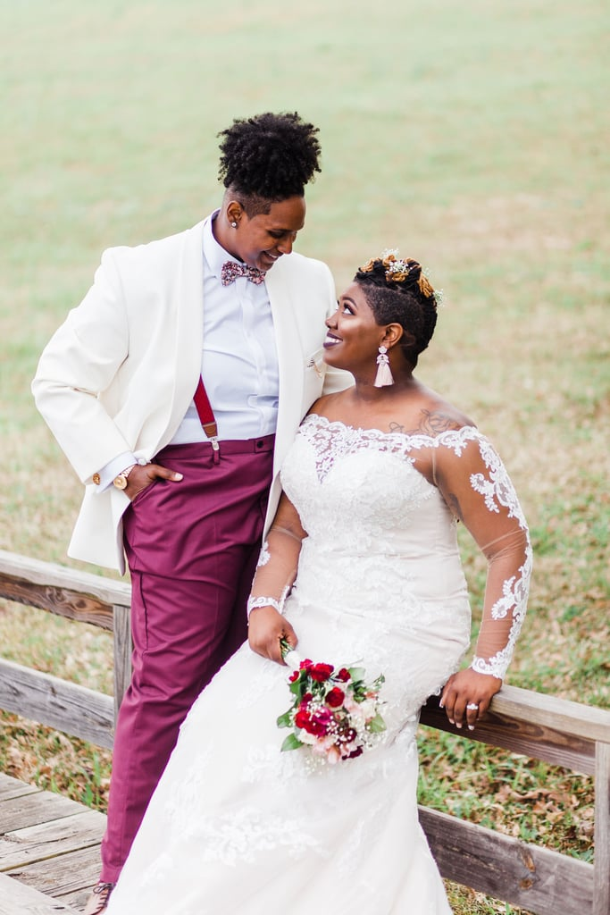 """Jaleesa and Amber knew each other long before before they fell in love. The two grew up in small towns that were just 10 miles away, and they crossed paths countless times over the years with their overlapping interests, from church choir to basketball. The couple officially met when Amber was hosting an event through her nonprofit organization and Jaleesa attended to show her support. Soon after, Amber reached out to Jaleesa on Facebook and told her how beautiful she thought she was. """"She claimed she was just letting me know, but she was running game lol,"""" Jaleesa wrote in an email to POPSUGAR. Since then, the two have been inseparable. """"Marriage was [and] is important to both of us, and it was something we discussed at the very beginning,"""" Jaleesa said. """"One day as we were talking, we shared our Pinterest wedding inspiration and it was the same stuff!"""" While the pair agreed on the theme for their April 2019 wedding, which they described as rustic-vintage-bohemian, Jaleesa took on all the decor duties to save money, and the hard work (and late-night YouTube tutorials) paid off. From the wood signage to the circular ceremony arch and """"foreva eva"""" cake topper, every detail came together beautifully. This is even more impressive considering they had a major change of plans just days before the big day. The couple had originally planned to have an outdoor wedding in their backyard, but due to a last-minute change in weather, they had to find a new venue. Just three days before the ceremony, Jaleesa and Amber secured a charming farmhouse in Greenville, SC, which was the perfect outdoor setting for them to host their intimate group of wedding guests. Jaleesa walked down the aisle in a romantic off-the-shoulder lace dress, while Amber rocked a stylish white suit jacket with burgundy pants. Before the wedding, Jaleesa gave Amber a small pin that she could wear inside her jacket. """"The pin included photos of some of her dear family members whom she would have wanted to be th"""