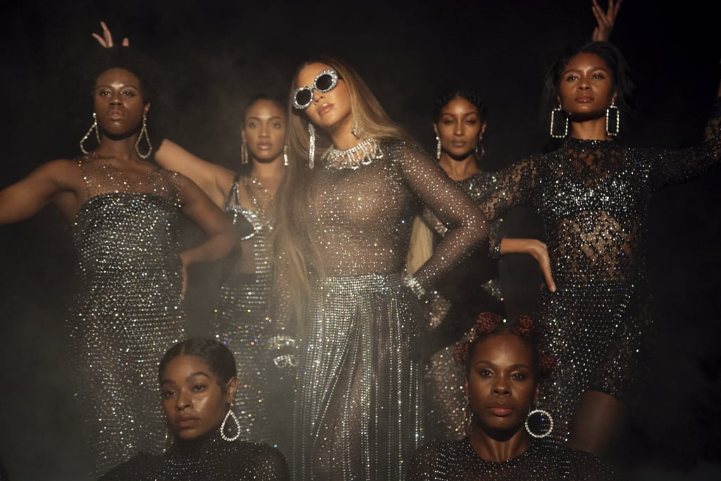 Beyoncé wears a Destiney Bleu catsuit, skirt, and gloves, Area arm ties, necklace, and crystal headpiece, A-Morir sunglasses, and Alessandra Rich earrings.