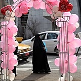 An Iraqi woman walks past an arch decorated in pink, red, and white balloons in Baghdad.
