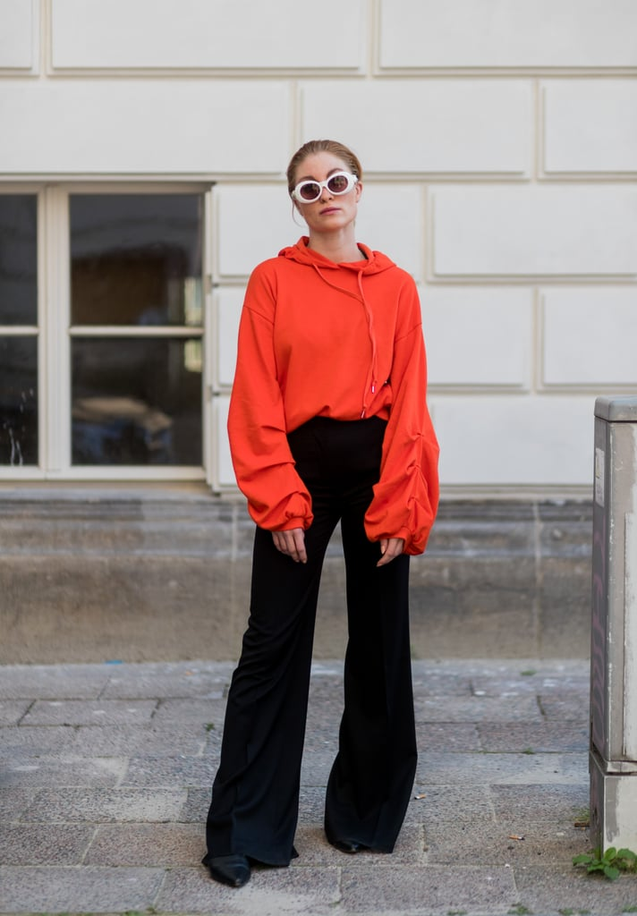 Give Off Subtle Festive Vibes By Tucking an Orange Top Into Black Bell Bottoms