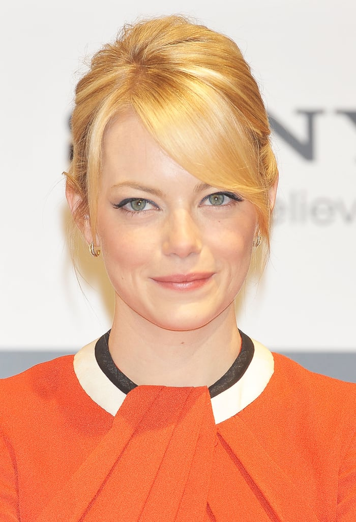 Emma Stone wore an orange dress with a black and white collar to the press conference for The Amazing Spider-Man in Japan.