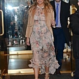 Wearing a floral Zimmermann dress, a beige jacket, and Saint Laurent rope sandals.