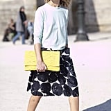 A retro-inspired print, cut, and socks and heels combo gets a modern update via a bright, oversize clutch.