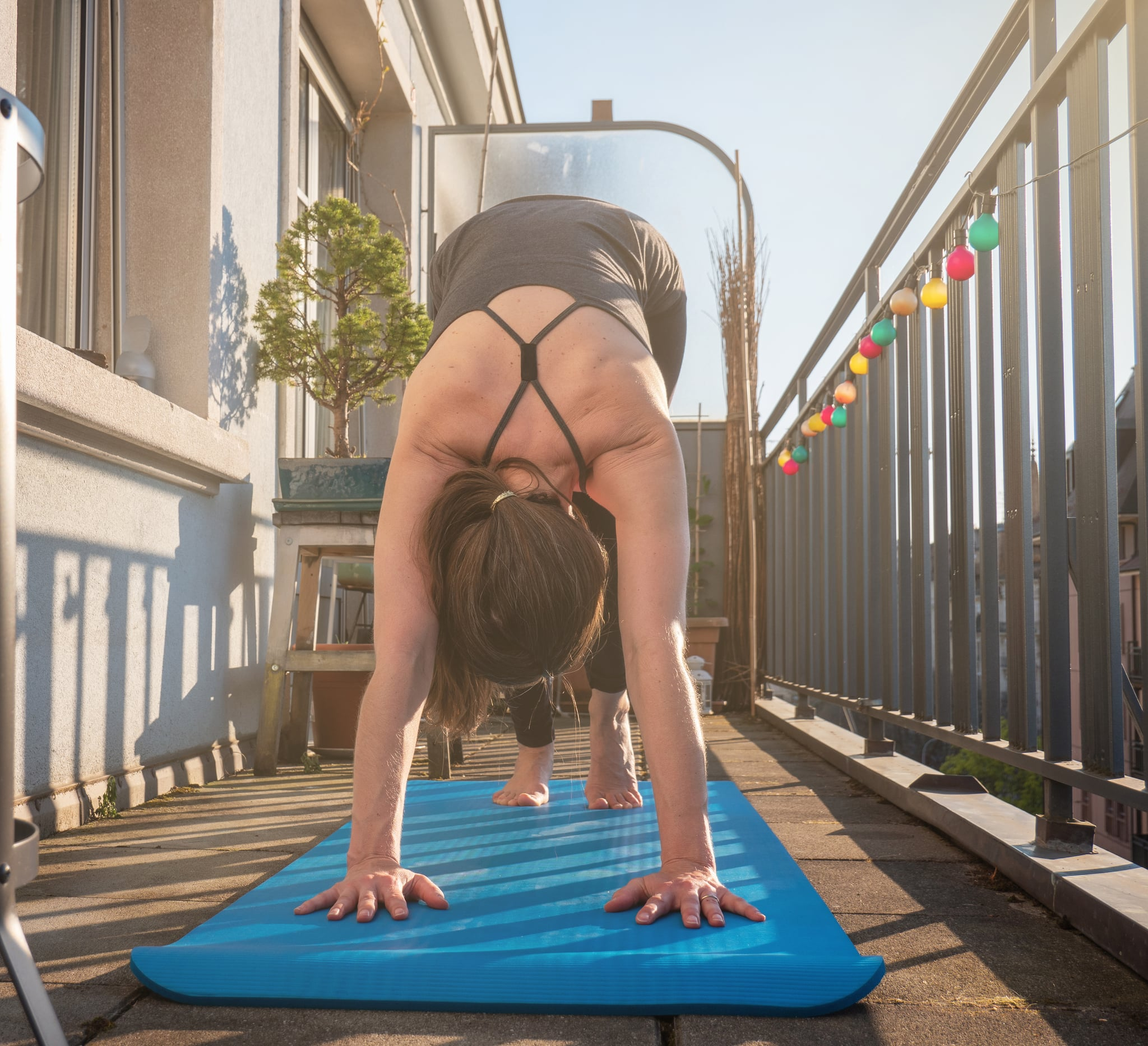 A woman practices yoga on the balcony of her apartment during the Covid-19 lock down in Geneva, Switzerland. The sun shines on the balcony as she maximizes the space available to work out from home.
