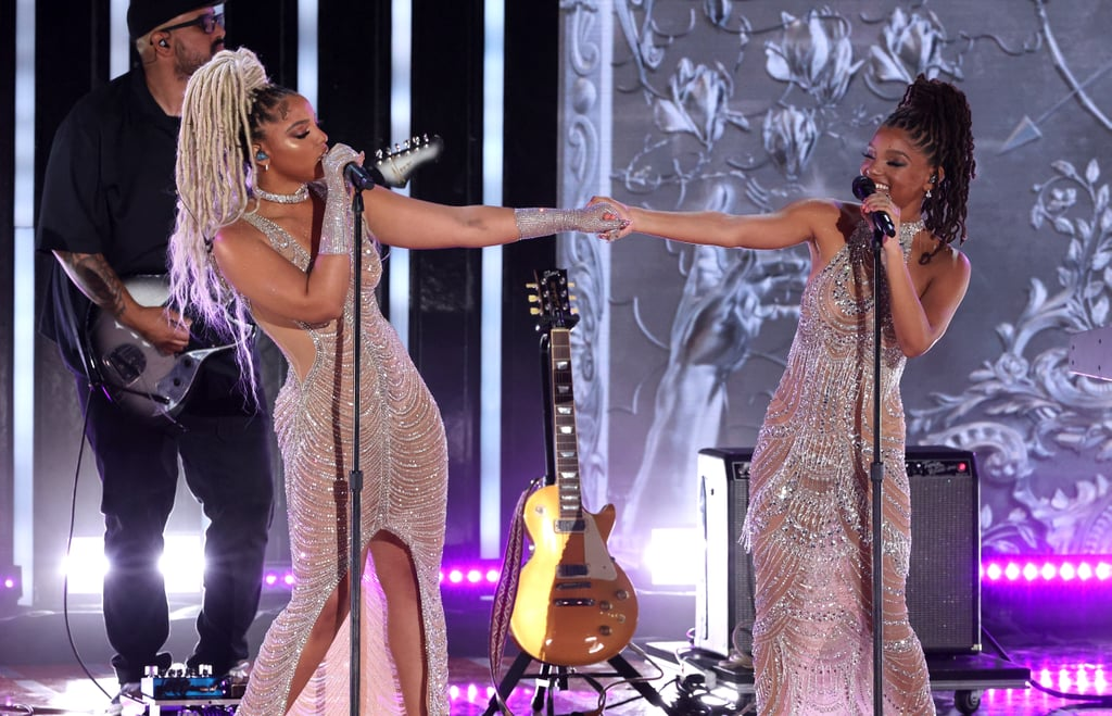 """Chloe and Halle Bailey took the stage at Global Citizen Live in New York on Saturday, and the sisters delivered a vocal performance that was just as stunning as their designer gowns. During impassioned renditions of """"Do It"""", """"Cool People"""", and """"Baby Girl"""", they glided across the stage in sheer Yousef Al Jasmi dresses that created the illusion they were dripping in diamonds.  Chloe and Halle paired the bedazzled outfits with nude heels and matching braided ponytails. For a little extra sparkle, Halle also adorned her fingers with silver rings, while Chloe slipped on a pair of bejewelled gloves that blended in seamlessly with her dress. Like the chandeliers out of Beauty and the Beast come to life, the sisters were radiant from every angle. See Chloe and Halle's stunning dresses here.       Related:                                                                                                           I'm Surprised the Billowing Sleeves on Lady Gaga's Velvet Gown Didn't Send Her Flying Away"""