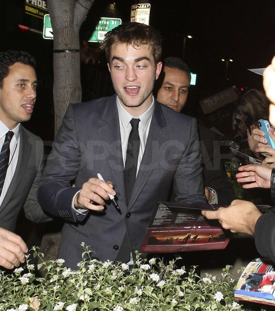 Robert Pattinson stopped to sign autographs.