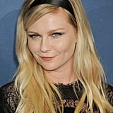 Kirsten Dunst paired a lace dress with a silky ribbon headband. To complete the black trifecta, she wore an oblong smoky eye shadow look.