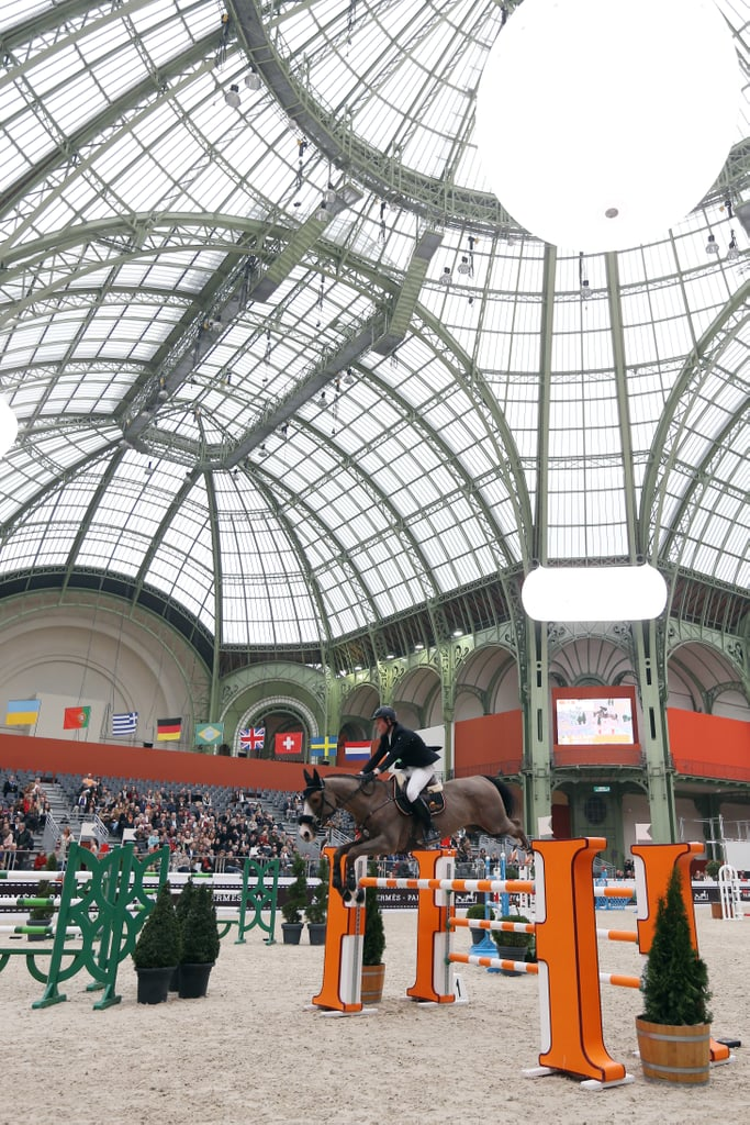 A horse competes under the intricate ceiling of the Grand Palais in Paris.