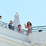 Eva Longoria waved to fans below as she posed on a rooftop for a photo shoot at the Cannes Film Festival.