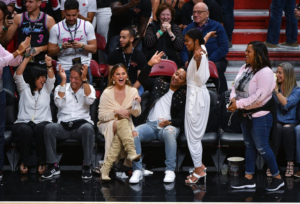 "It was an emotional night for Miami Heat fans as Dwyane Wade said farewell to the American Airlines Arena for his final regular season home game before retiring. But for Chrissy Teigen and John Legend, who were sitting court side with Gabrielle Union, it turned out to be a bit of a wet evening, too. John and Chrissy were cheering on their close friend, Gabrielle was screaming for her man and squeezing his butt, and Dwyane was knocking down shots for his 30-point game versus the Philadelphia 76ers. But in the midst of all of this, he tried to drill a three-pointer from inside the sideline when he came crashing in between Chrissy and John. Whoops!  In a now-viral photo, the shooting guard collapsed right on top of friends, and tequila soda (presumably) splashed everywhere. Except, Gabrielle did point out, ""@johnlegend did not, I repeat, did not drop his drink. And this is why we are friends,"" she wrote alongside the iconic photo. Dwyane unfortunately missed the shot, but fortunately for us, it was all captured on camera. We just have to wonder: is that a foul on Chrissy or Dwyane? Regardless, the obvious victim here is the spilled drink. Ahead, see photos of Chrissy, John, and Gabrielle at Dwyane's final regular season home game, and note the reaction faces post-splash."