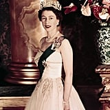 Queen Elizabeth II poses wearing a formal sash and crown in 1955