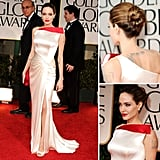 Angelina Jolie looks striking on the Golden Globes red carpet. She's wearing a silky white Atelier Versace gown with bright red neckline detailing, matching perfectly with her red clutch.
