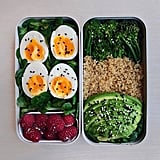 Soft-boiled eggs on fresh spinach with sides of quinoa, avocado, and greens.