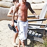 Shirtless David Beckham on the beach.