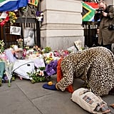 A woman knelt in front of the Nelson Mandela memorial in London.