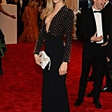 Cara Delevingne's studded plunging column dress, white studded clutch, and shoes were courtesy of Burberry.