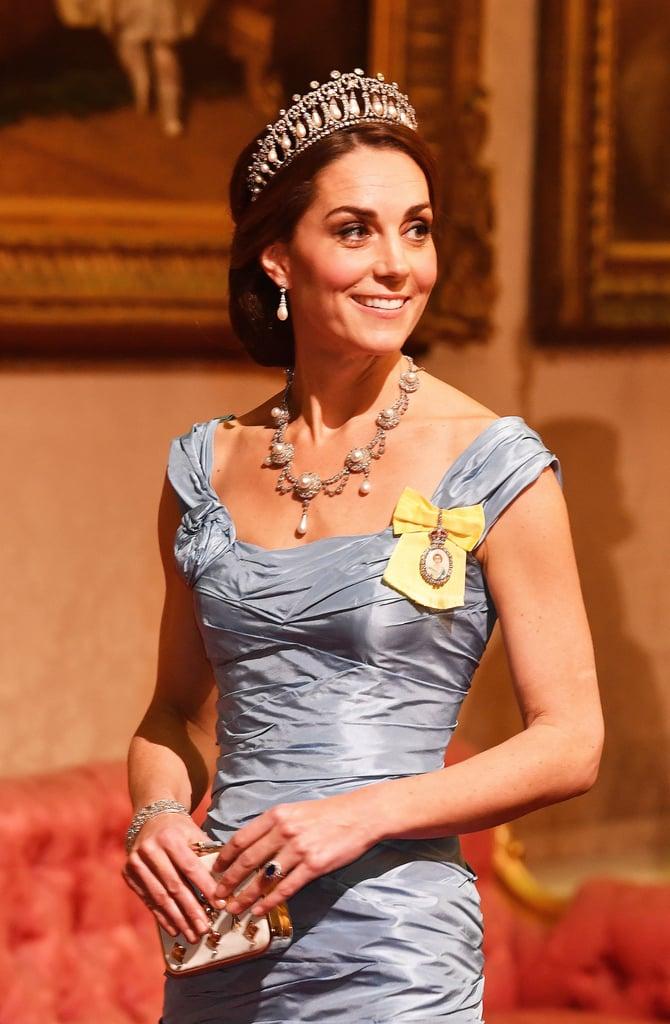 """تمتلك الدّوقة كيت ميدلتون مجموعة متميّزة من التيجان الملكيّة، لكن يبدو أنّها تعود دائماً إلى واحدٍ منها على وجه الخصوص: وهو تاج Cambridge Lover's Knot (عقدة العاشق). فأثناء حضور مأدبة رسميّة إلى جانب الأمير ويليام والملكة إليزابيث الثانية يوم 23 أكتوبر، أطلّت كيت مثل الأميرة سندريلا الحقيقيّة. إذ اختارت ثوباً أزرقاً من إبداع ألكسندر ماكوين، فيما أوحى اختيارها المتعلّق بالمجوهرات أنّها تفضّل الإكسسوارات الملكيّة ذاتها التي ارتدتها والدة زوجها الراحلة، الأميرة ديانا. هذا ولا تعتبر تلك المرّة الأولى التي تحيّي فيها كيت الأميرة ديانا بارتدائها للتّاج الفريد ذاك. حيث تألّقت بتاج """"عقدة العاشق"""" (من مجموعة الملكة ماري) لحضور حفلات الاستقبال الدبلوماسيّة في الأعوام 2015، و2016، و2017. وكانت  الملكة ديانا قد حظيت بالقطعة المرصّعة بالجواهر هذه كهديّة زفافها، وأصبحت الخيار المفضّل لدى الأميرة الراحلة، إلى جانب أقراط Collingwood  اللّؤلؤ المُلحقة به والتي تأخذ شكل القطرة. شاهدي أدناه صورة ديانا وهي ترتدي التاج والأقراط معاً، ثم تابعي القراءة لتري المزيد من اللّقطات للّدوقة كيت وهي تطلّ بالإكسسوارات ذاتها."""