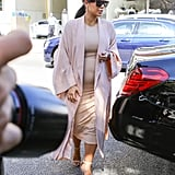 Body-conscious but not flashy, Kim stepped out in a blush-colored duster coat to polish off a tan dress.