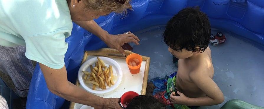 Grandma Feeds Grandkids While in the Kiddie Pool