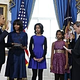 For the Sunday swearing-in ceremony held in the Blue Room of the White House, Michelle Obama chose the color du jour: blue. Wearing a printed Reed Krakoff sheath with a solid-hued cardigan and low black heels, Michelle looked every bit the polished FLOTUS.