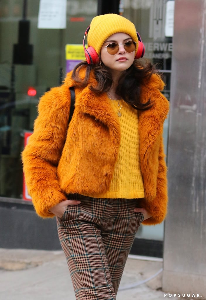 Selena Gomez looked like the embodiment of fall during her latest outing. The singer, actress, and budding beauty entrepreneur was recently photographed wearing quite the cosy outfit while filming Only Murders In the Building in New York City. Though we don't know much about the upcoming Hulu comedy series, we can already glean her character's love of seasonal dressing.  The mood-boosting outfit in question consisted of plaid trousers, a mustard sweater, and a very cute, cropped, furry coat in a similar orange-yellow shade. The accessories helped pull the look together, and included a matching knit beanie, round sunglasses, gold hoop earrings, and brown combat boots. See photos of Selena on set ahead, and if her fuzzy coat caught your eye, browse some similar options.       Related:                                                                                                           18 Winter Style Essentials We'll Have on Repeat All Season Long