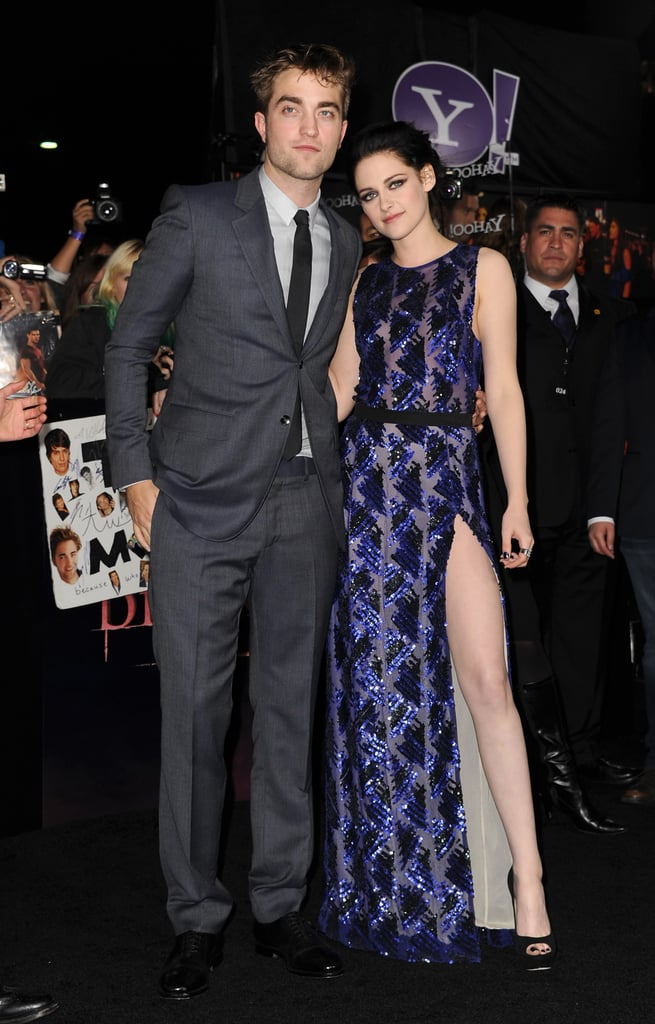 """Kristen Stewart and Robert Pattinson arrived together and stayed side-by-side at the LA premiere of Breaking Dawn Part 1 in LA this evening. Kristen was showing off lots of leg with a very high slit in her J. Mendel dress, which was long, blue, and gorgeous. She started out the black carpet in peep-toe heels, but she swapped them out for sneakers after posing for pictures. Robert stuck close by her side as the two smiled for the hundreds of fans who camped out for days leading up to the premiere. Robert and Kristen reunited in LA this week after he spent time in NYC promoting the movie on talk shows while she logged in a few more days on the set of Snow White and the Huntsman in the UK.  On the Breaking Dawn black carpet we chatted with both Robert and Kristen about saying farewell to the series that has dominated their lives over the past few years. Kristen told us that she already feels like she has said goodbye to Bella Swan, but that she'll always have the memories. Robert, on the other hand, says what he'll miss the most is his costars. Kristen revealed that she imagined her Twilight wedding """"a million times,"""" though she never thought about the dress so she was relieved to see what Carolina Herrera designed for the momentous occasion."""