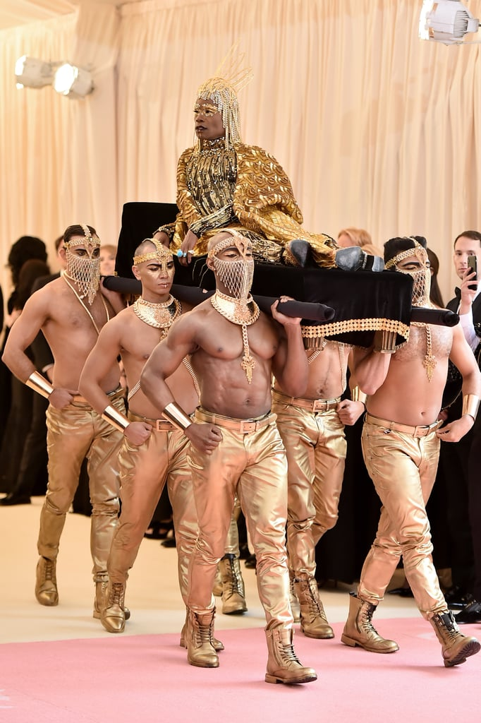 Billy Porter knows how to make an entrance — after all, this is the same man who took the Oscars red carpet by storm earlier this year in a custom-made Christian Siriano tuxedo gown that put everyone else to shame.  But the Pose star and Broadway legend one-upped himself at the Met Gala on Monday as he arrived atop a velvet chaise being carried by. . . [counts on fingers] six handsome, shirtless men in gold lamé pants. As one of the first stars on the red carpet for the camp-themed event, it's safe to say that Billy set the bar pretty high; and if that wasn't enough, he completely owned the carpet while showing off his ornate fringe jumpsuit and sequinned wings. Keep scrolling to see Billy's insanely glamorous entrance, then check out more of the campy Met Gala looks!