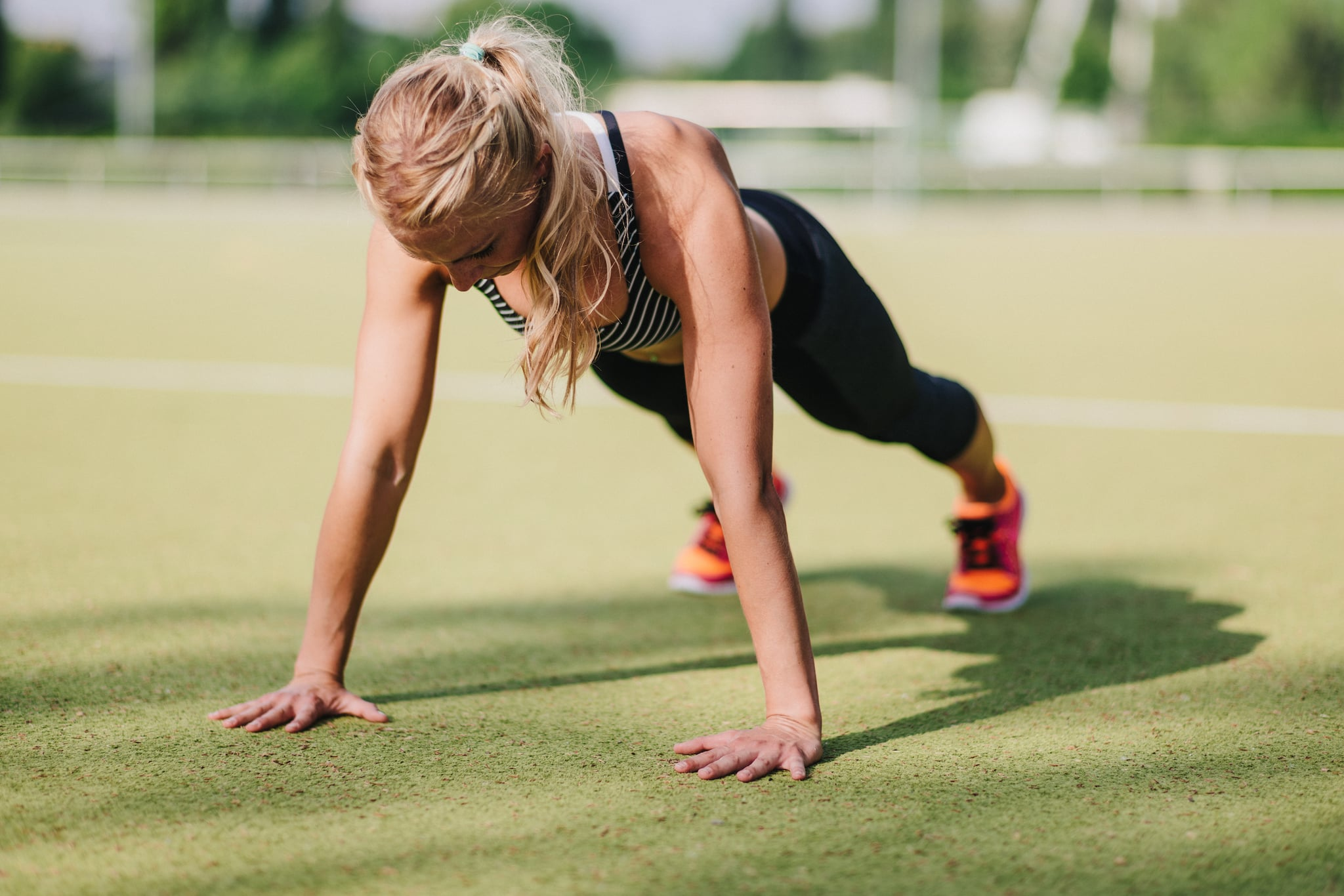 Blond haired woman doing pushup or press-up on a sports field.