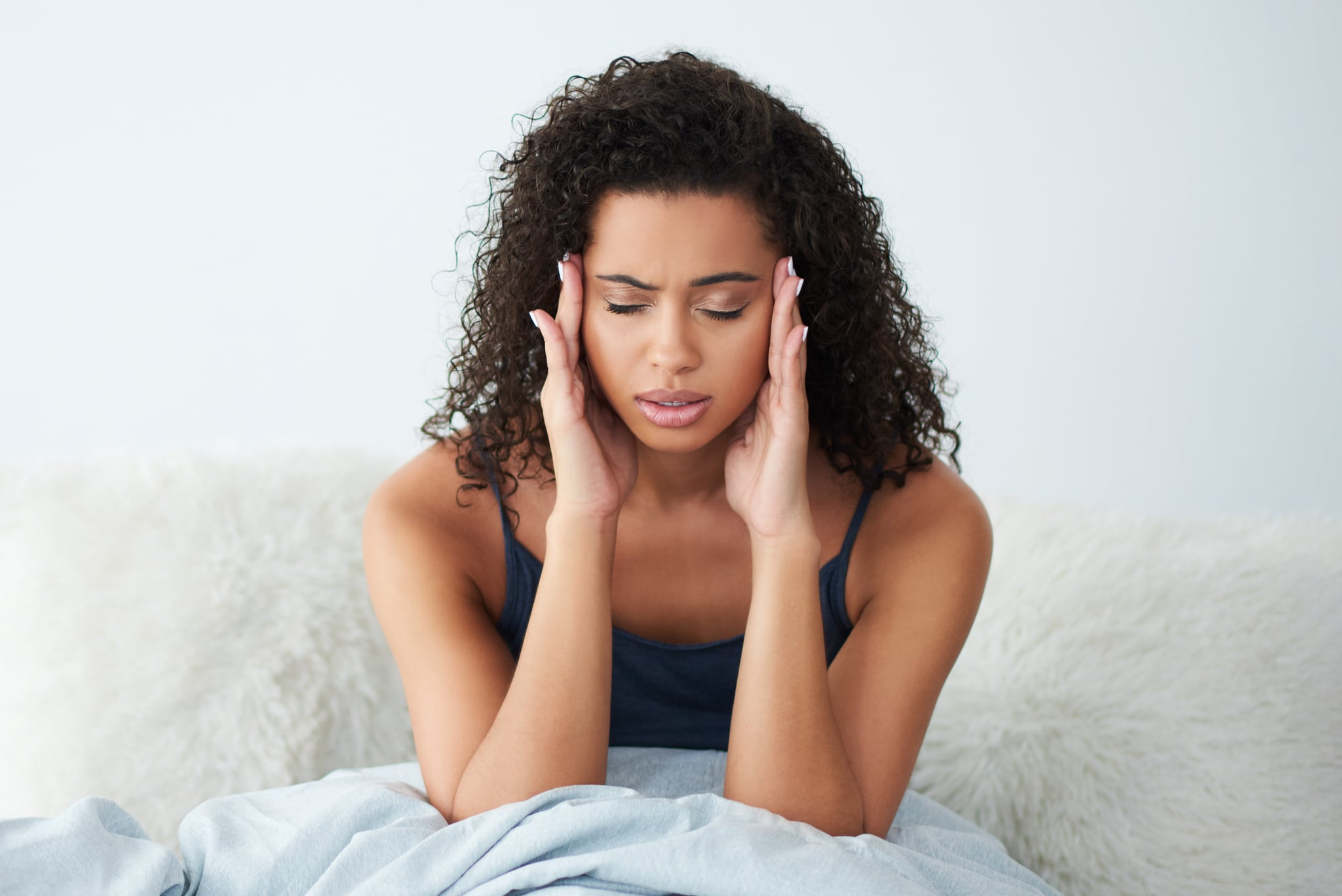 Shot of an attractive young woman suffering from a headache and rubbing her head while in bed