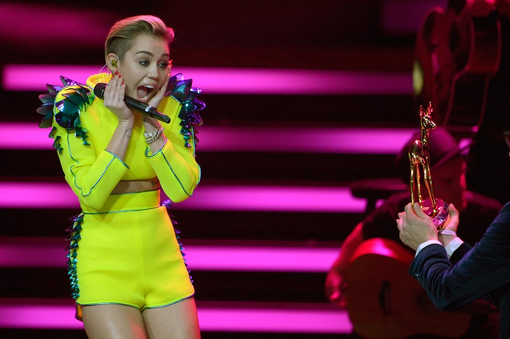 "Miley Cyrus channeled her inner Taylor Swift when she squealed in surprise upping seeing her adorable new award during the 2013 Bambi Awards in Berlin on Thursday. Miley was honored in the international pop category and performed for the audience after changing out of a demure Jean Paul Gaultier black dress and into a neon ensemble. Victoria Beckham was also honored at the event under the fashion category and got presented with her award by legendary designer Karl Lagerfeld. The pair exchanged air kisses on the stage and later posed for photos together with Victoria's award on the red carpet. Other honorees include Robbie Williams and Bill and Melinda Gates.  Miley has been causing quite the stir in Europe over the past week. On Sunday, she made headlines when she lit up a joint while accepting an award at the MTV EMAs in Amsterdam. The singer's hectic schedule may be taking a toll on her, as she tweeted right before the award show that she is starting to feel sick. ""All this traveling is finally taking its toll on me,"" Miley wrote."