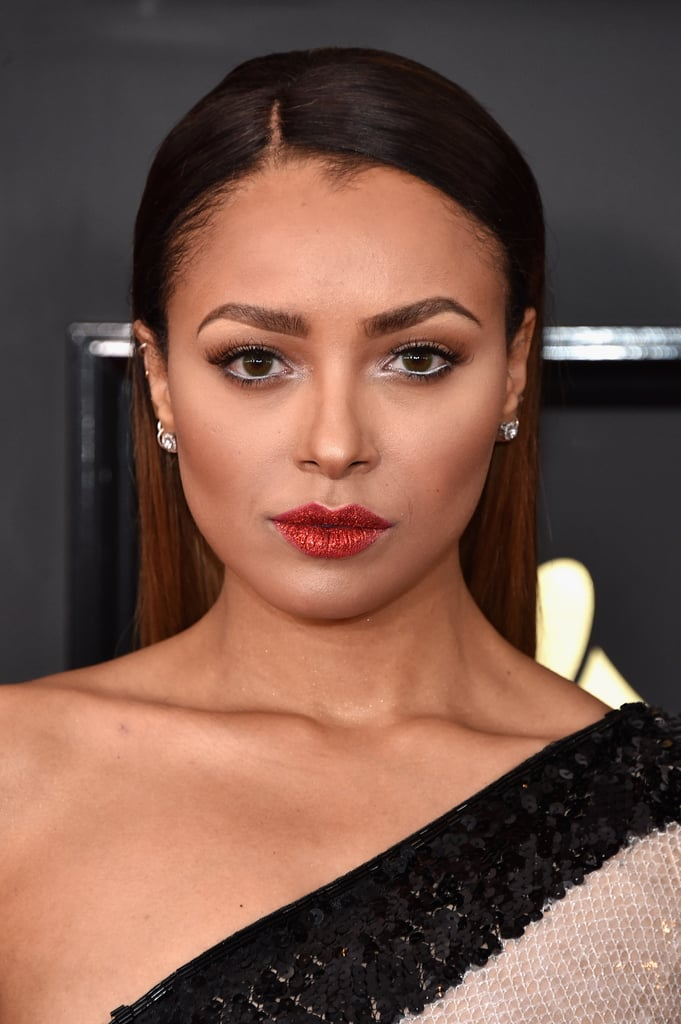 Kat Graham was practically dripping in glitter from head to toe at the 2017 Grammys. The Vampire Diaries star rocked red-hot sparkly lips that perfectly matched the bold hue on her striped one-shoulder dress. Her sleek and simple hairstyle allowed her dazzling lips to steal the show.  This isn't the first time we've seen this shiny makeup trend, as it has made appearances on the runway and social media. Plus, with Pat McGrath's glitter lip kit, nailing the sparkly fad is easier than ever. Read on for an up-close look at Kat's glittery lips on the Grammys red carpet.