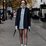 With a Grey Jumper Dress, a Striped Coat, and Silver Ankle Boots