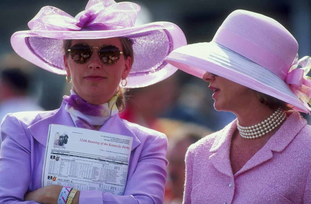 Two female spectators dressed in pink suits talked as they watched the track during the Kentucky Derby in 1993.