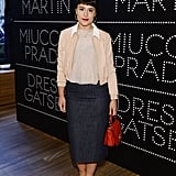 Jessie ware wore a peach sweater with white collar, blouse, navy pencil skirt and a red handbag.
