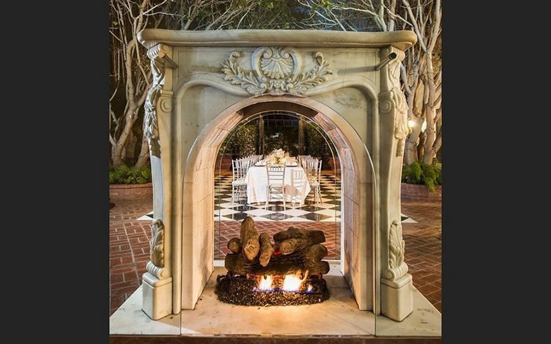 A freestanding outdoor fireplace adds elegance and whimsy to the outdoor dining patio.