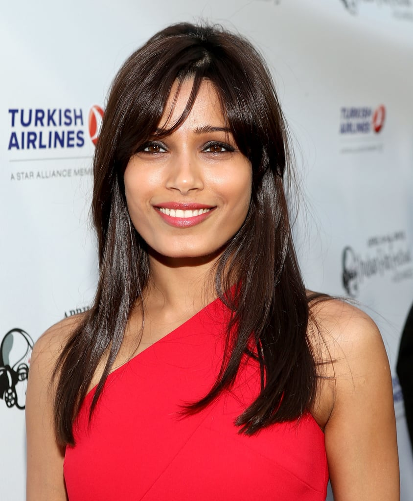 At the Indian Film Festival of Los Angeles, Freida Pinto arrived in a bold red dress, which she wore with long parted bangs, gray eye shadow, and a touch of sheer red color on her lips.