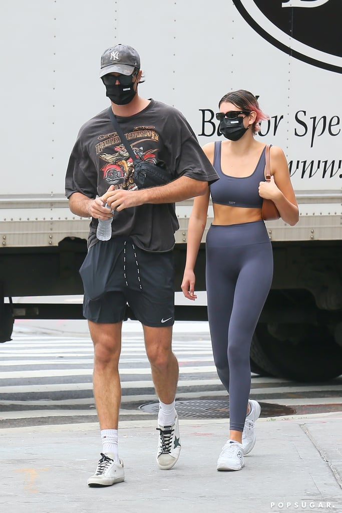 While comfort is always the number-one priority in a workout outfit, looking cute comes in as a close second for me, 'cause sometimes a fun matching set is the extra push you need to get to the gym. Kaia Gerber checked all the boxes in a flattering workout set on her way to NYC gym Dogpound with rumored boyfriend Jacob Elordi. The model always manages to look effortlessly cool, whether it's in a metallic mesh dress or casual athleisure, and her 'fit from this outing was no different. After being spotted getting cozy at dinner the night before, Kaia and Jacob headed to work out on Sept. 9 in relaxed gymwear and matching black face masks. Kaia wore a cool gray sports bra with a square-cut neck and high-waisted seamless leggings from Set Active, a brand she's sported often while working out from home on Instagram Live, as well as at Dogpound.  The 19-year-old model, whose recently dyed pink hair peeked out from her messy pony, paired the set with some New Balance dad sneakers. She accessorized with oval-shaped Ray-Ban sunglasses and a simple brown baguette bag. Ahead, get a closer look at Kaia's full outfit and shop her exact leggings and top.