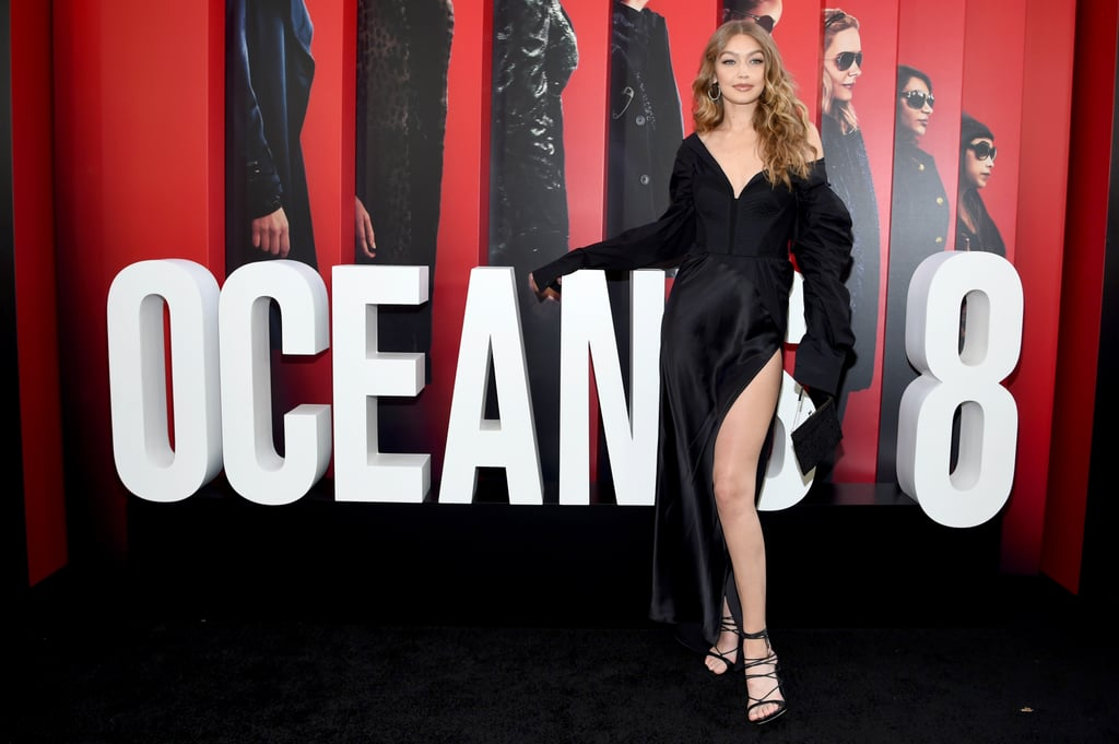 Gigi Hadid's red carpet style needs no introduction.  The 23-year-old model walked the Ocean's 8 premiere red carpet in a sultry leggy gown, which begs the question — what can't she do? She can go from a full-on colourful bodysuit one night to a sexy revealing gown the next and nobody will bat an eye. That's because she's a seriously stylish icon.  Her chic black off-the-shoulder gown appeared modest on one side but featured a thigh-high slit on the other that seemed to go on for miles. She paired the gown with strappy black heels and Lorraine Schwartz earrings and rings. Ahead, see Gigi's dress from all angles, even the ones that will leave you breathless.