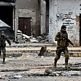 Military forces walk through Syria during a military operation on Dec. 14 that resulted in shelling and air strikes.