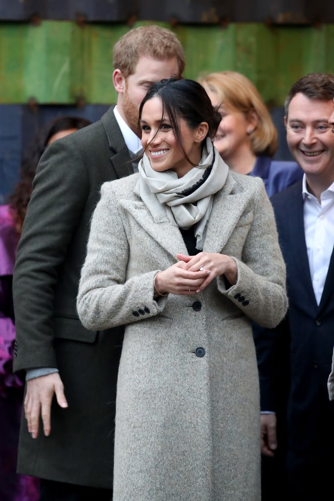 On Tuesday, Meghan Markle and Prince Harry made their first official public appearance of 2018 when they visited the studios of Reprezent 107.3 FM, an underground music station that supports young people through creative training. For the occasion, the royal fiancée wore a now-sold-out long Smythe coat over a black Marks & Spencer sweater, black Burberry high-waisted flares, and patent court shoes. She then accessorised her outfit with a Jigsaw scarf, three thin rings, a matching bracelet, and, of course, her stunning engagement ring. This isn't the first time that Meghan has been seen wearing this coat. Back in April 2016, she wore it in a different colour while on the set of Suits with a pair of black ripped Paige jeans and Birdies slippers. Could she be taking a cue from the Duchess of Cambridge, who's known for recycling her royal gear? Read on to get a closer look at her outfit and shop similar coat options.