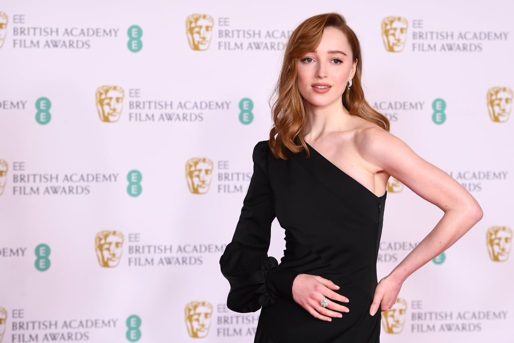Phoebe Dynevor has arrived — literally, professionally, sartorially. The Bridgerton actress attended the 2021 BAFTA Awards on Sunday to present the outstanding debut category, and she herself made an outstanding debut when she rolled up to the red carpet, popped her head out of the SUV she'd arrived in, and proceeded to pose for quite the photo series — her feathery waves flapping in the wind and the hem of her custom gown blessing the earth beneath her.  Styled by Nicky Yates, Phoebe's red carpet look consisted of a silk black Louis Vuitton dress with an asymmetrical, one-shoulder neckline. The dress was paired with a diamond ring and emerald earrings also by the brand. The sleek look is a far cry from the frilly, Regency-era dresses Phoebe wore as the Duchess of Hastings — although there's absolutely a market for that, too, with replicas of the character's signature blue gown now popping up on Etsy.  Take a closer look at Phoebe's latest glamorous appearance ahead.      Related:                                                                                                           Priyanka Chopra's Elegant Butterfly Gown at the BAFTAs Is Entirely Made From Recycled Materials