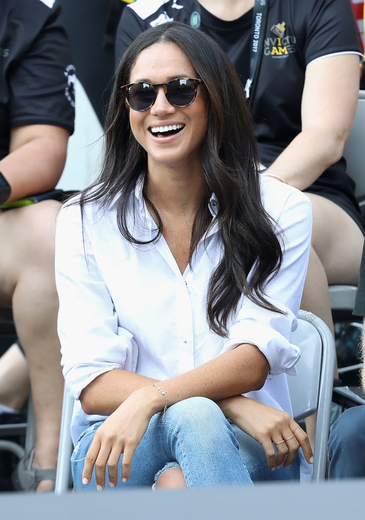 Her penchant for the style dates back to her and Prince Harry's first public appearance as a couple at the Invictus Games in 2017, where she wore Misha's Husband Shirt with a pair of distressed skinny jeans. Since then, Meghan has worn similar styles on numerous occasions, from casual outings to Zoom meetings.