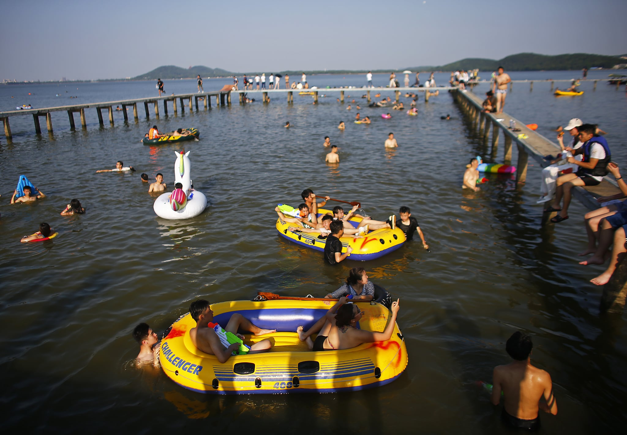 WUHAN, CHINA - JULY 24:  Residents enjoy the water in East Lake of Wuhan, Hubei province, China, July 25, 2016. This activity, which requires participants to ride their bikes and jump into the lake, attracts many extreme cycling enthusiasts from the city, local media reported. Picture taken July 18, 2015 on July 24, 2016 in Wuhan, China.  (Photo by Wang He/Getty Images)