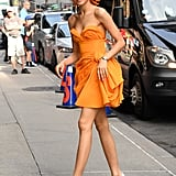 Zendaya was seen wearing an orange strapless Carolina Herrera dress with a bow headband to a taping of The Late Show With Stephen Colbert. She finished off her look with white pumps and gold earrings.