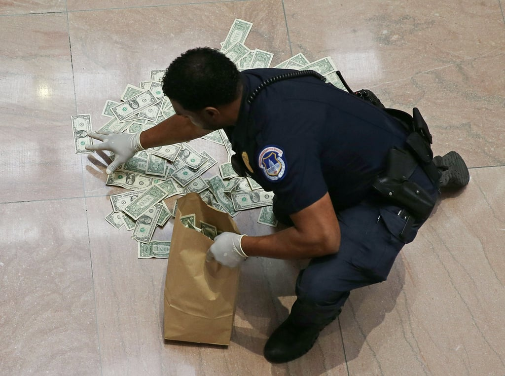 A US Capitol policeman picked up money that was thrown by activists at the Hart Senate Office Building in Washington DC.